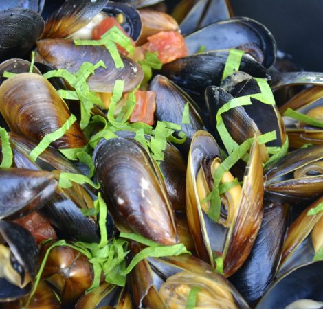 Ravda, Bulgaria. May, 24,2014. Sea mussels in wine sauce with a pinch of green onion in black pan. Traditional food.